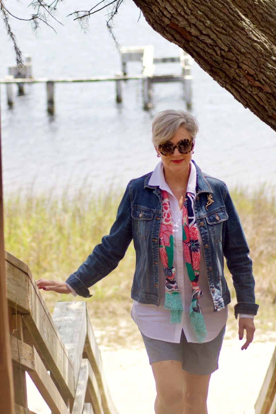 beth from Style at a Certain Age wears a white shirt, chambray shorts, jean jacket and scarf at Panama City Beach