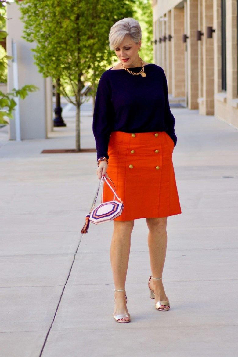 beth from Style at a Certain Age wears a J.Crew orange skirt, blue tee, gold sandals, and Tory Burch mini bag.