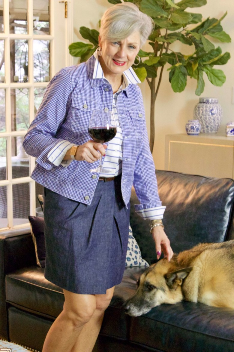 beth from Style at a Certain Age wears a gingham jean jacket, striped shirt, denim skirt, espadrilles and wicker handbag