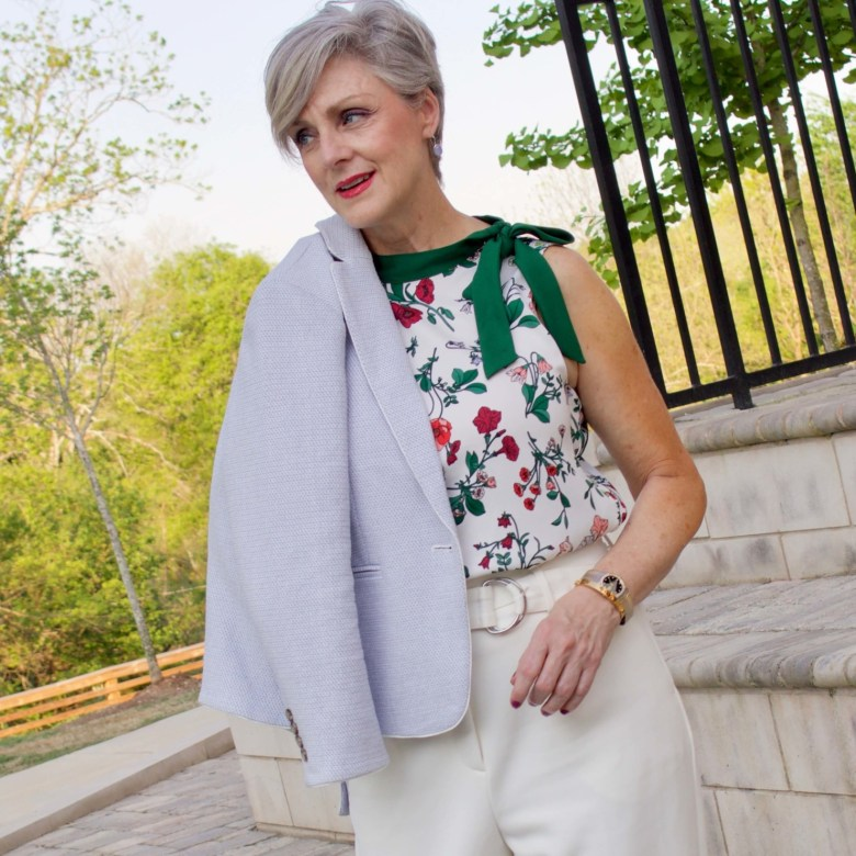 beth from Style at a Certain Age wears a textured blazer and floral sleeveless blouse