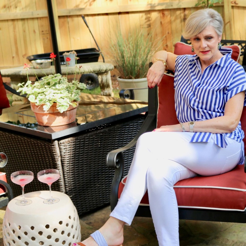 beth from Style at a Certain Age wears a striped shirt, white denim, and seersucker sandals