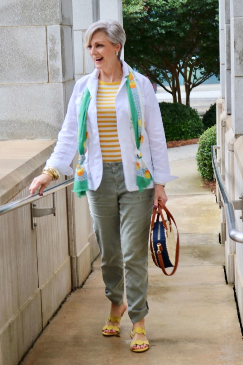how to wear a jacket for spring and summer beth from Style at a Certain Age wears a white utility jacket, striped tee, green utility pants, yellow sandals, lemon scarf, and cornhusk handbag