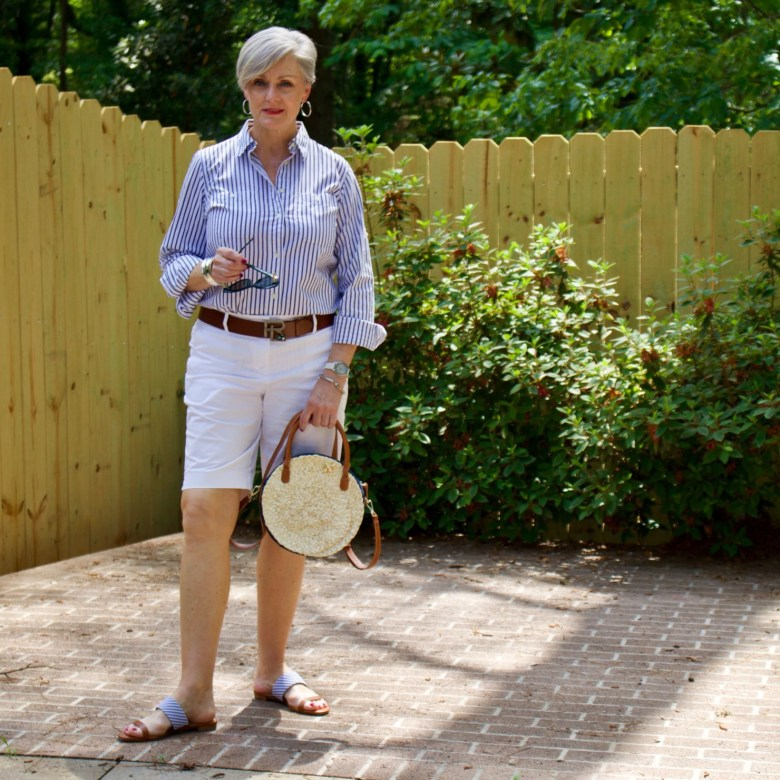 beth from Style at a Certain Age wears a striped shirt, white shorts, sandals, and rattan handbag