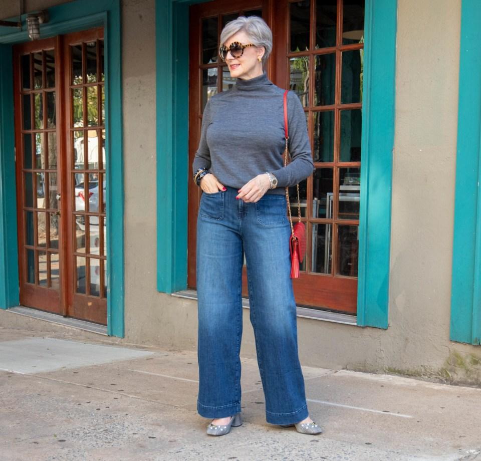 wide leg jeans, gray turtleneck, red handbag