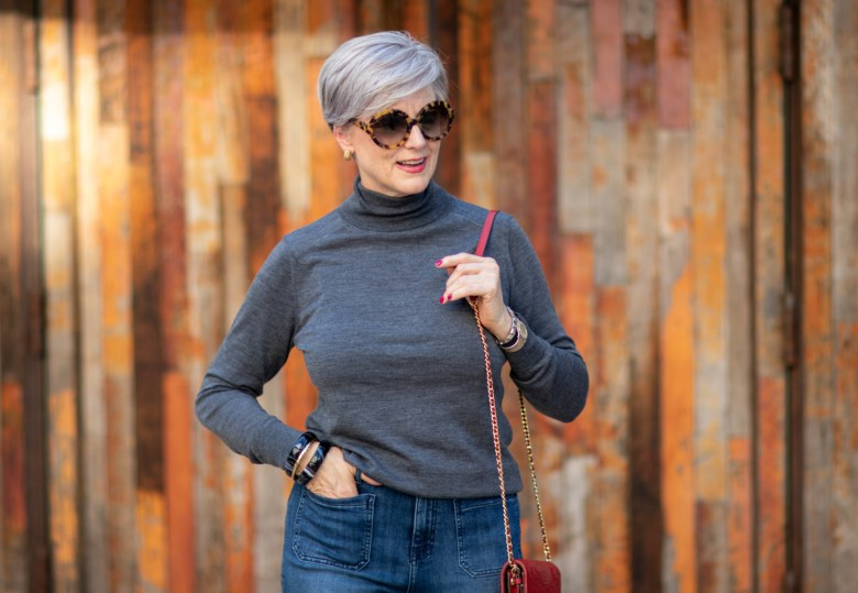 wide leg jeans, gray turtleneck, red handbag
