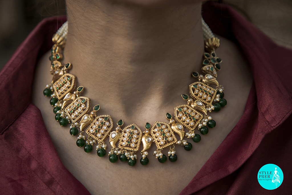 Gold Plated Silver Choker With Leaf Silhouette And Bird Motifs Studded With White And Green Stone In A Pearl Mala.