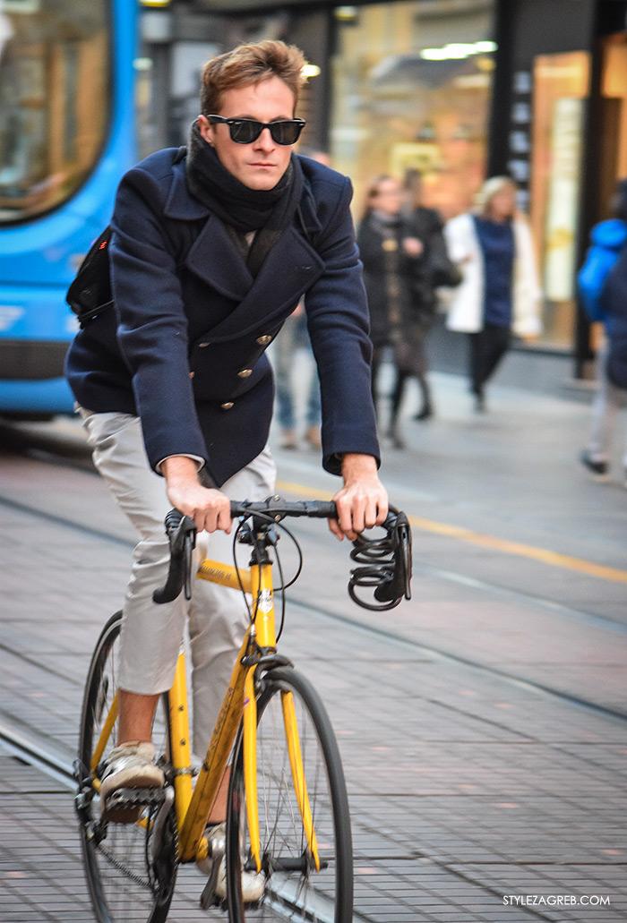 Street Style Zagreb muška moda navy peacoat mornarska jakna muškarac na Ilici u plavom mornarskom kaputiću sa crnim sunčanim naočalama na žutom biciklu street style