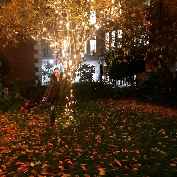 girl standing against tree with lights