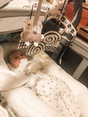 baby laying in travel cot