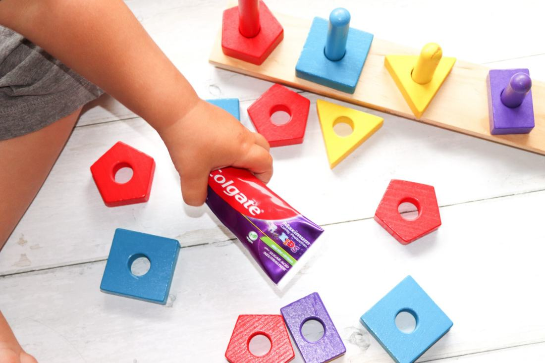 toddler holding toothpaste and building blocks