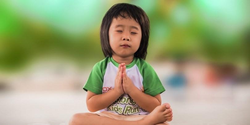 Menina sentada e praticando a gratidão.