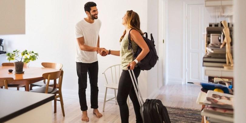 Duas pessoas se cumprimentando quando mulher chega na casa alugada, sendo uma fonte de renda extra para o rapaz.