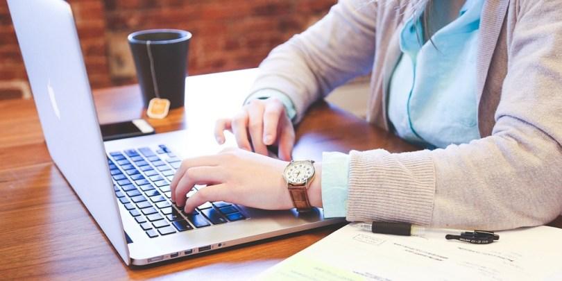 Mulher mexendo no notebook, podendo indicar que ela está preenchendo alguma pesquisa online e gerando renda extra para ela.