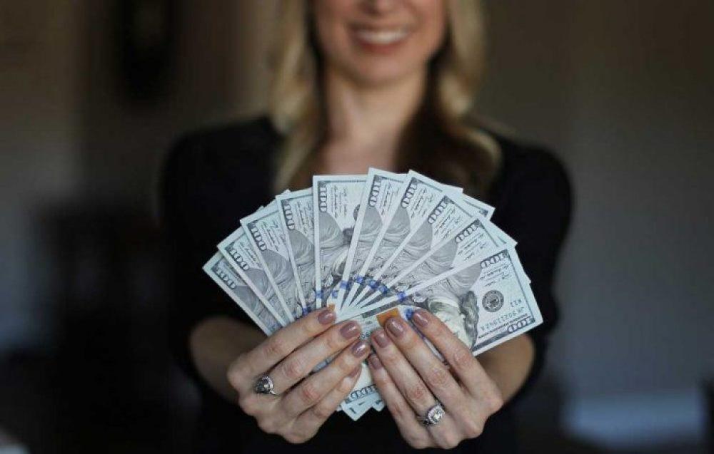 Mulher segurando dinheiro na mão, o que economizou fazendo o controle de gastos.
