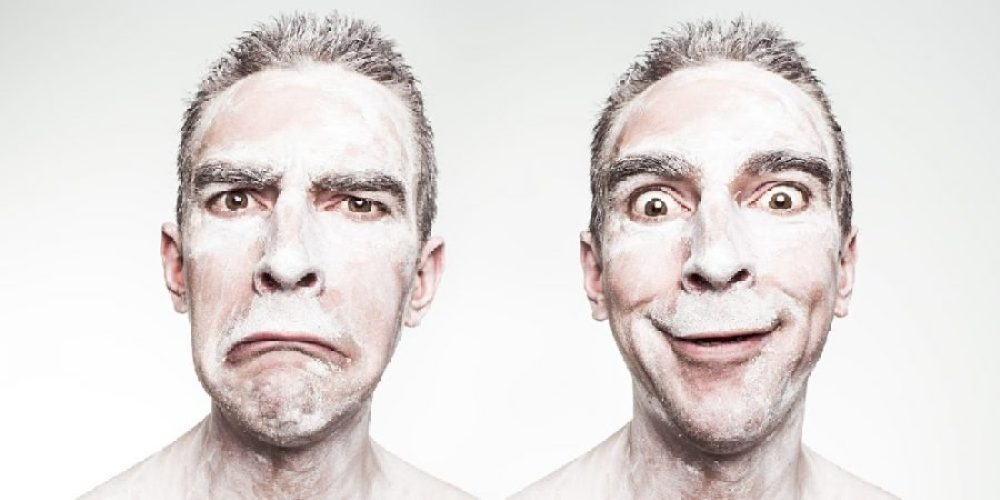 Dois rostos demonstrando dualidade da personalidade financeira, mão de vaca e mão aberta.