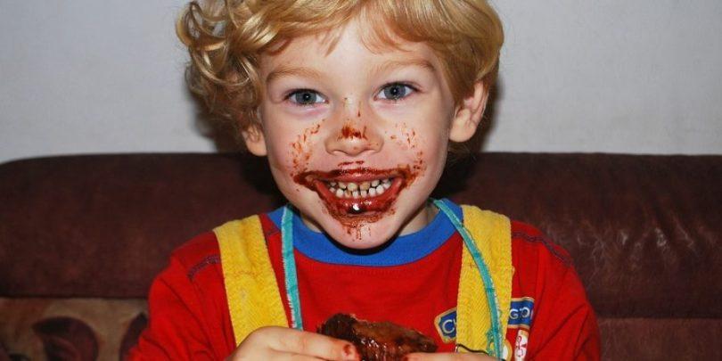 Criança comendo bolinho com alegria porque pensaram em economizar na festa infantil dele.