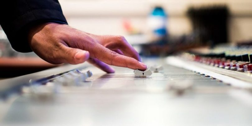 Homem controlando uma mesa de som, representando um dos hábitos milionários, o controle do dinheiro.