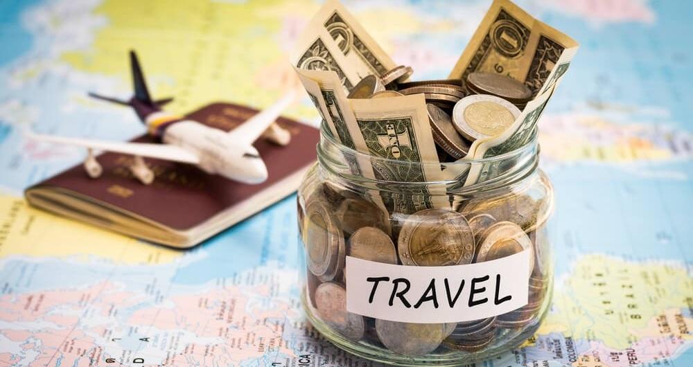 Pote de moedas, um mapa e um avião, mostrando a poupança que está sendo feita com foco em viajar, mas que não basta apenas ganhar mais dinheiro pra acelerar esse objetivo.
