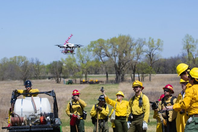 The drone takes off on it's 5th flight of the test surrounded by the UNL drone team, media and firefighters. UNL researchers use a small drone to set prairie burn at Homestead National Monument in Beatrice, NE. April 22, 2016. Photo by Craig Chandler / University Communications