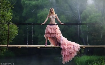 Naked Photographs - woman in pink skirt with no top on a bridge