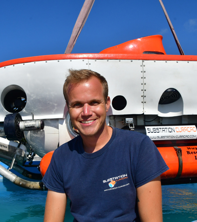 Jordy Stolk a Dutch substation Curaçao pilot loves the underwater world is smiling towards the camera in front of the submarine.