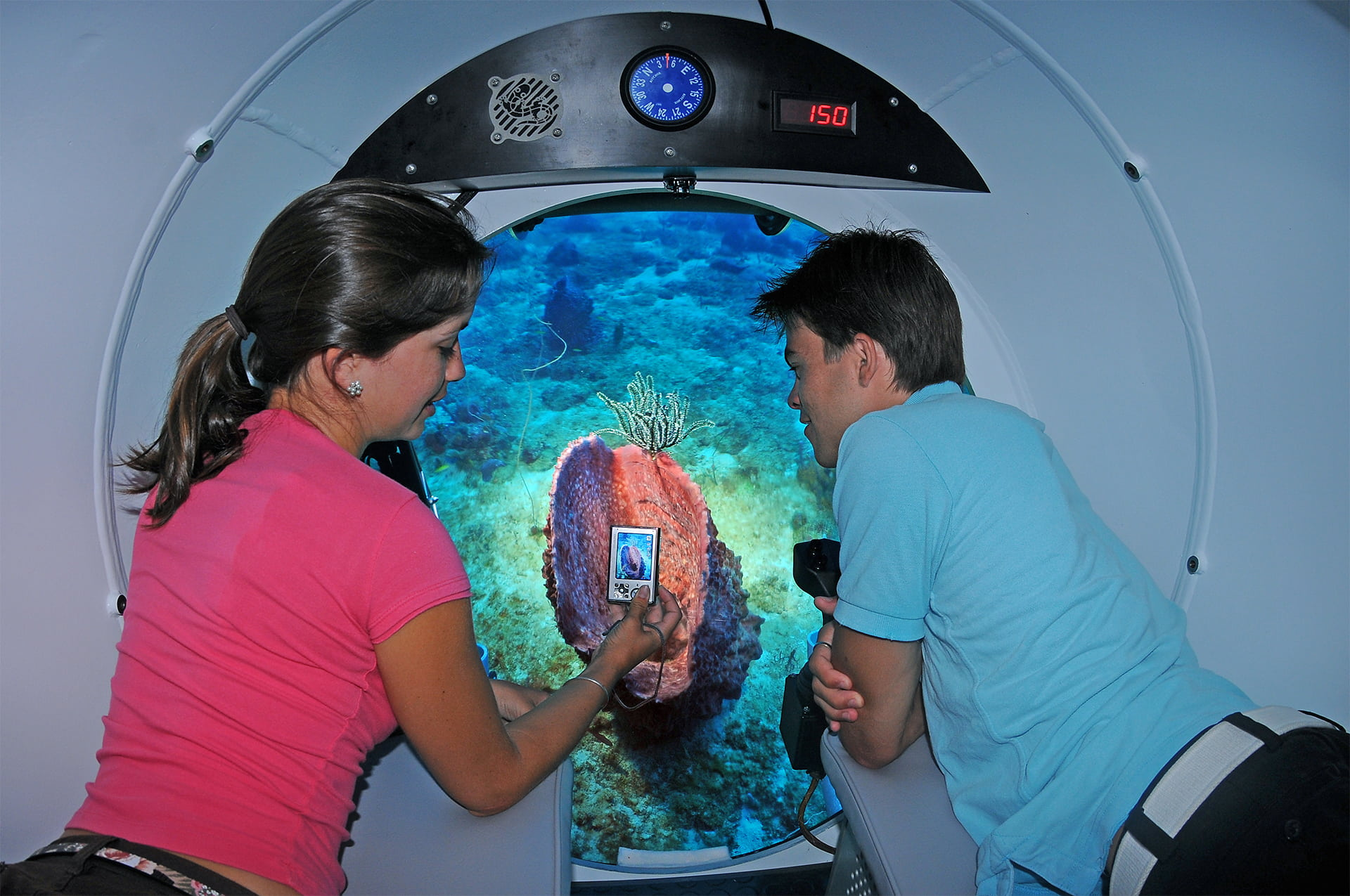 Two young tourist's underneath Curaçao inside a submarine capturing a picture from window of amazing underwater spectacles.