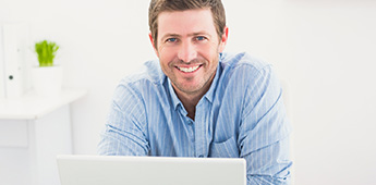 Smiling man using a laptop computer