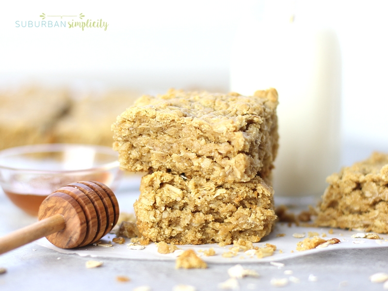 Two Oatmeal Bars stacked on each other with a glass of milk in the background.