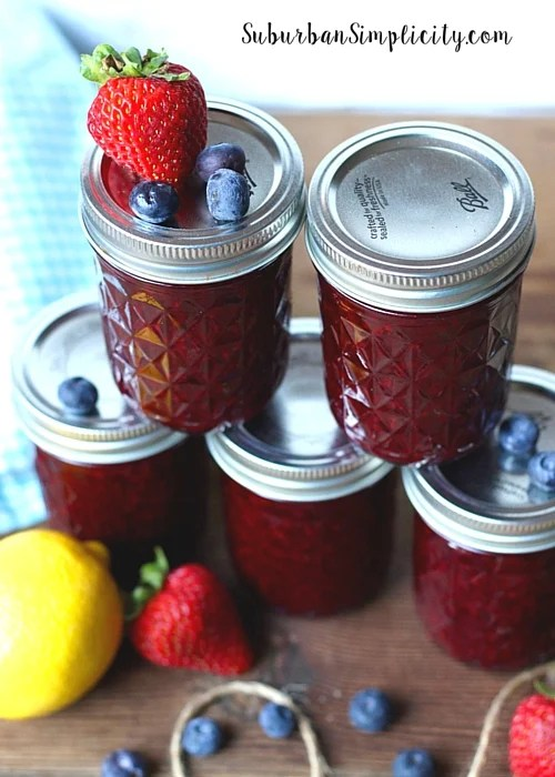 Five mason jars of canned Mixed Berry Jam.