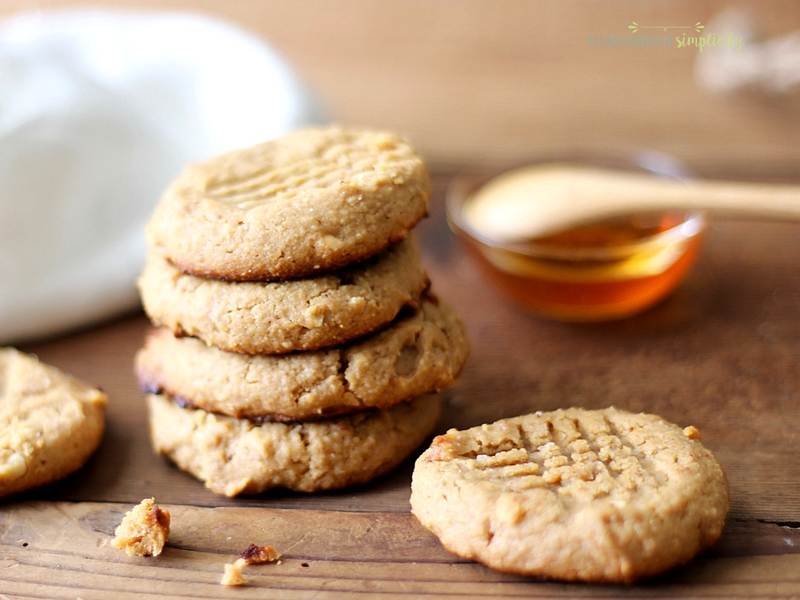 Baked gluten free almond flour peanut butter cookies sitting on a counter with honey in the background.