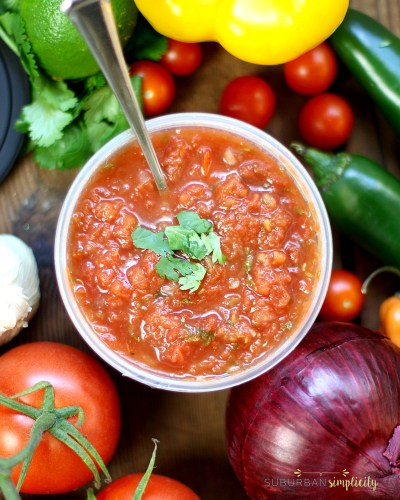 Fresh refrigerated salsa surrounded by peppers, onions and tomatoes.