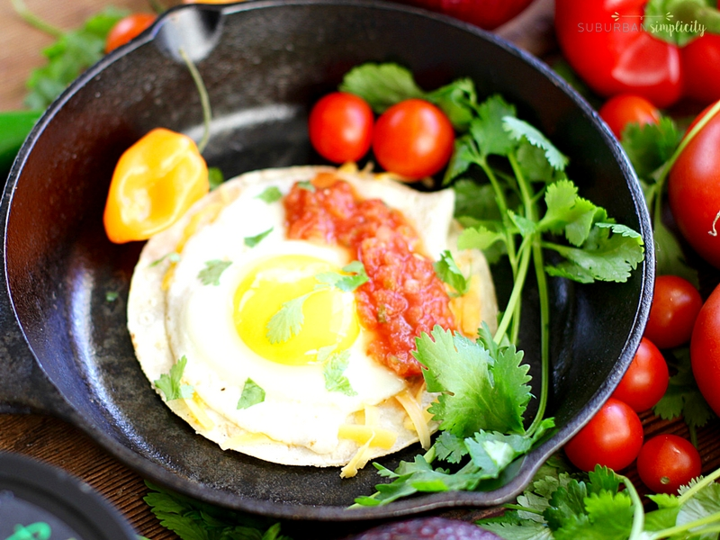 Cast Iron pan with fried egg topped with cheese and salsa.