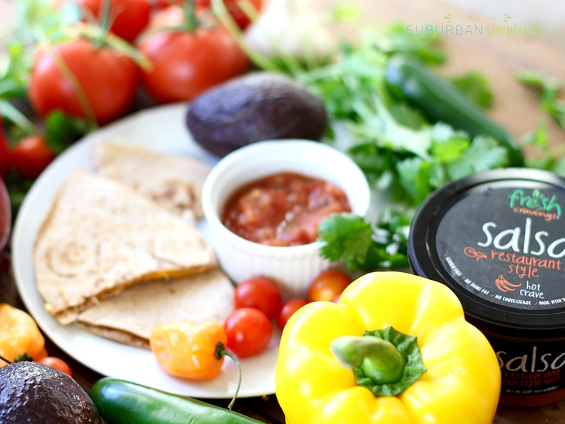 cheese quesadilla surrounded by fresh vegetables and fresh salsa.