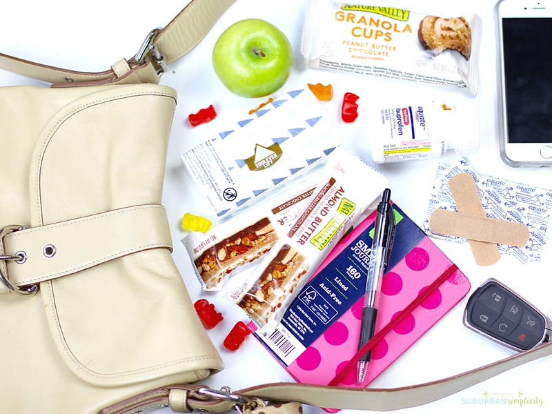 Grab and go essentials for family scattered around a purse.