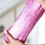 Pink glitter slime stretched by a girl's hands.