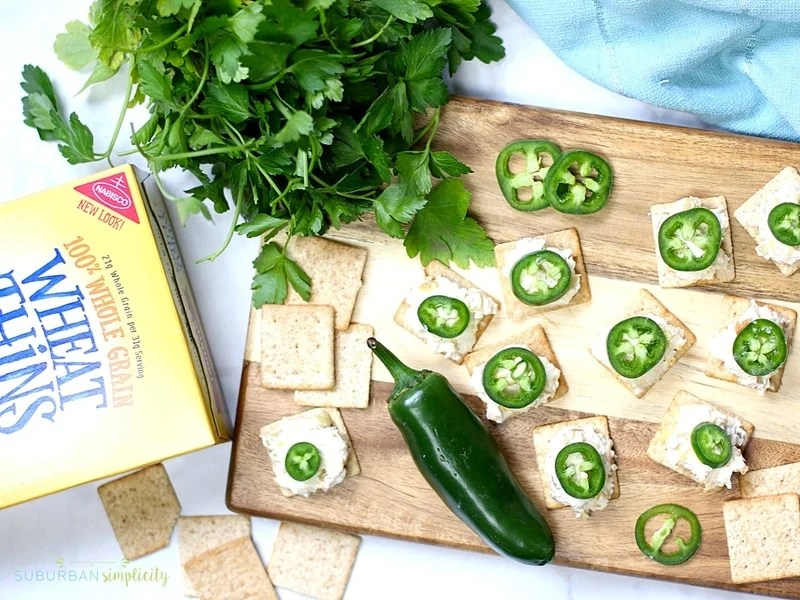 Jalapeno Popper Toppers on a cutter board with a fresh jalapeño and Wheat Thins.