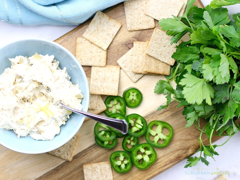 Jalapeno Popper Topper ingredients on a cutting board with crackers.
