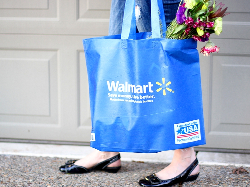 Mom standing with Walmart bag full of flowers.