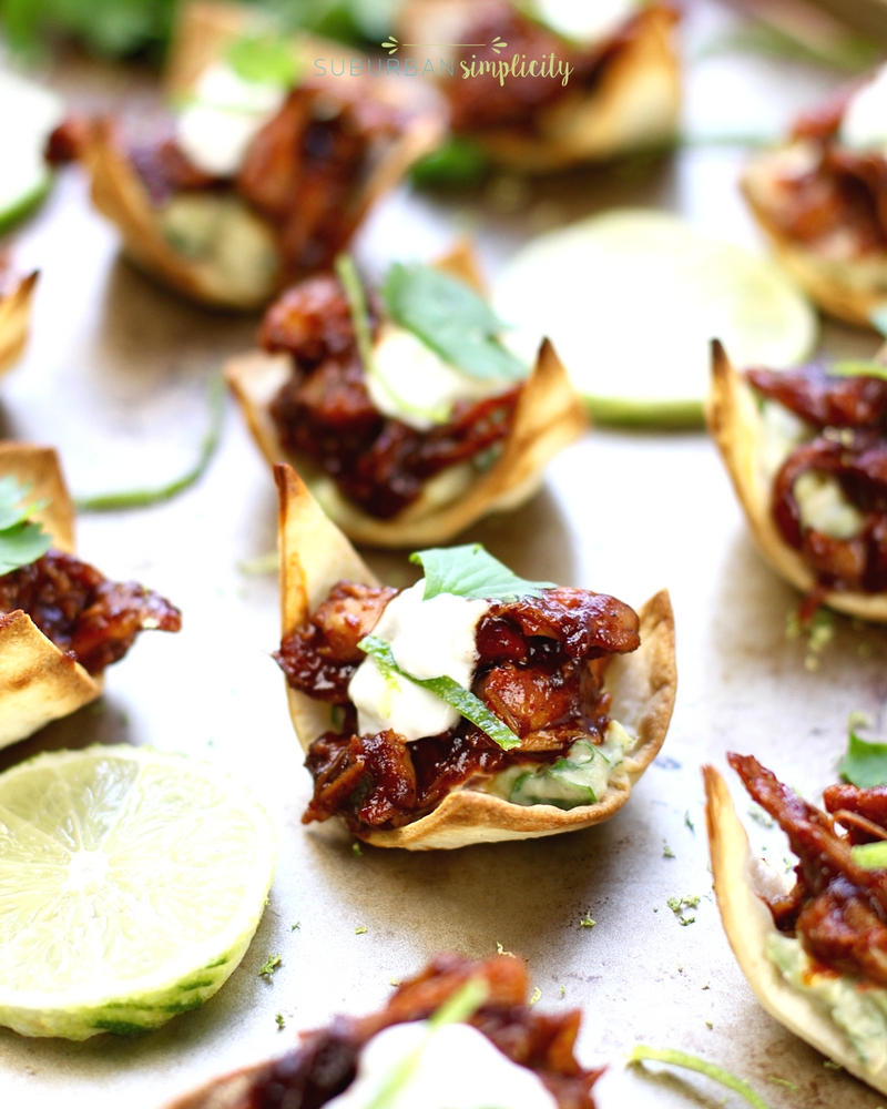 Chicken chipotle tostas on a serving tray next to a lime.