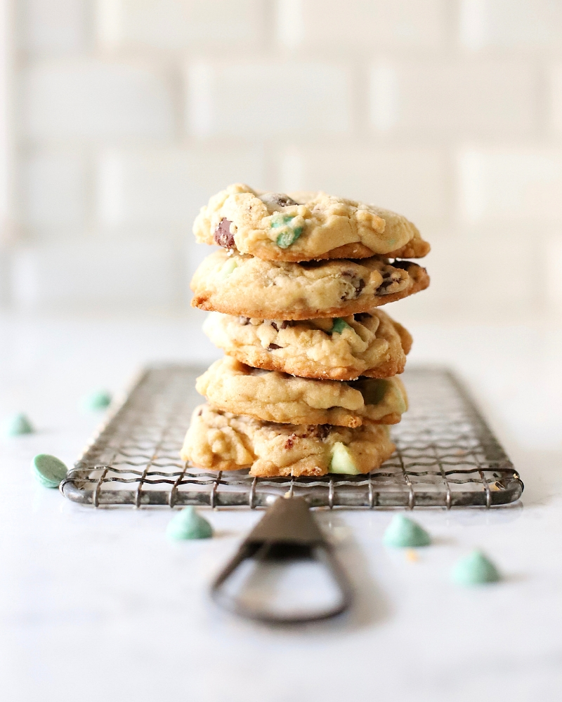Mint chocolate chip cookies stacked on a cooling rack.