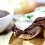 Crockpot French Dip sandwich next to a delicious dipping sauce.