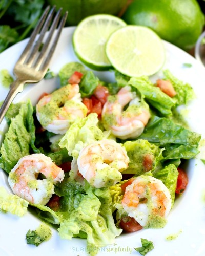 Avocado Cilantro Lime Shrimp Salad in a bowl with lime wedges on the side.