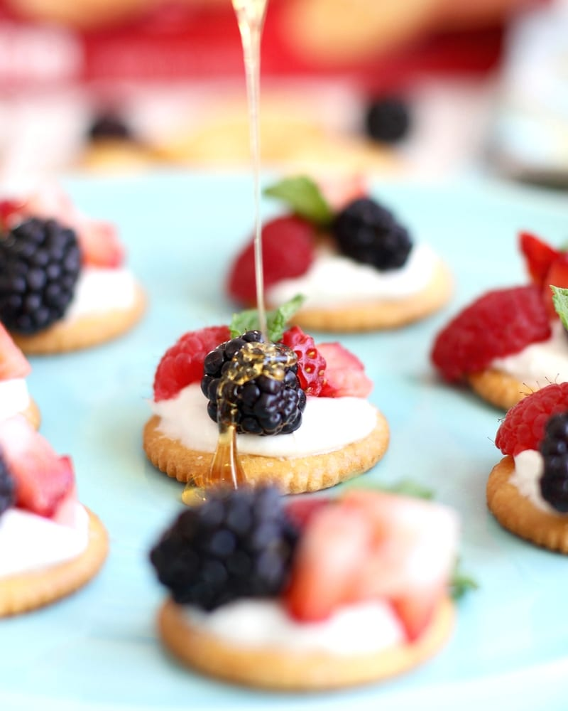 Ritz Crackers being with berries and cream being drizzled with honey
