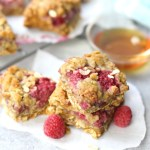 Raspberry oatmeal bars stacked together with fresh raspberry scattered about