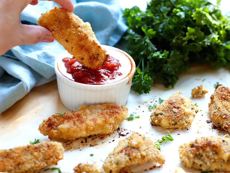 Easy chicken tenders being dipped in Marinara sauce.
