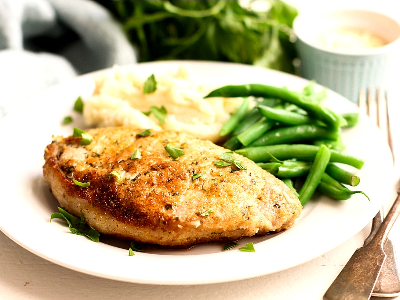 Parmesan Pork Chops on a plate with mashed potatoes and green beans.