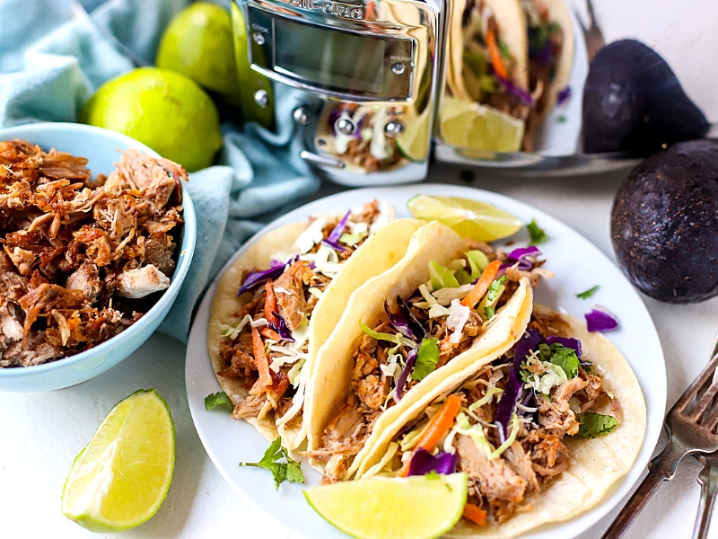 Crock Pot Pulled Pork Tacos in front of a slow cooker.