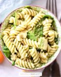 Close up photo of pesto pasta in a bowl.