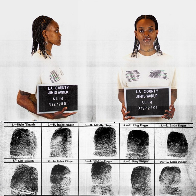 Woman holding inmate booking sign for last prisoner project campaign