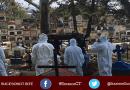 Personas en un cementerio con trajes especiales enterrado a un fallecido por COVID-19